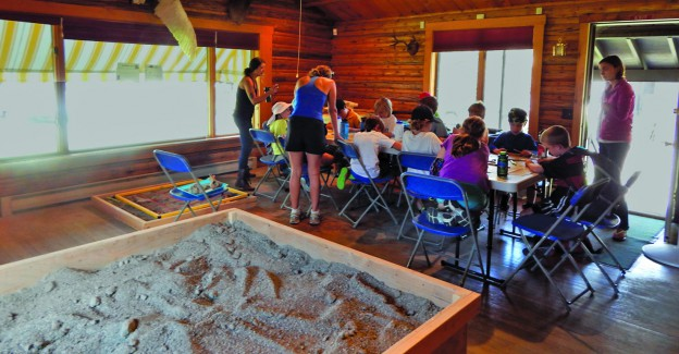 Class works on crafts next to mock archaeological dig