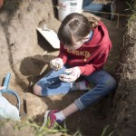 Jackson Hole Middle School student Ruby Erskine examines a small rock dug up at the archaeological site.