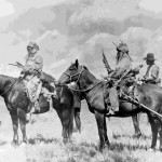 174. Men on horseback with regalia or costumes for 4th of July parade One with travois