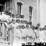 190. Rev. Roberts with students outside dormitory building at mission school