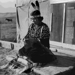 37. Shoshone woman in elk tooth dress sitting in front of wall tent cabin