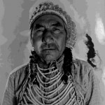 55. Indian man in war bonnet and beaded breastplate