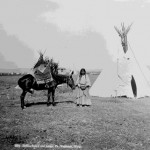 "58. ""Indian Squaw and Lodge, Ft. Washakie, WY"" Post card – woman holding horse with traditional saddle in front of tipi, more tipis and wall tents in distant background"