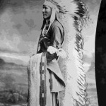 60. Man in full length war bonnet and rifle – posed shot