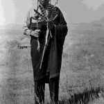 78. Man standing outside with ceremonial rattle and fan