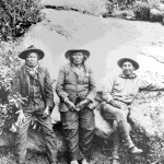 79. 3 Indian men leaning against a rock