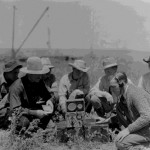 86. Men in field around radio transmitte