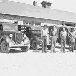 90. Men and trucks in front of stone Government buildings Fort Washakie