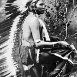 101. Posed studio shot of Indian warrior in full war bonnet with trailer kneeling