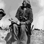 127. Washakie seated outside in chair hat in hand