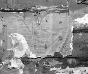 Remnants of old newspaper insulation on a cabin.