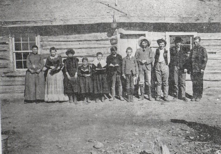 The first school class in Jackson Hole, outside Sylvester Wilson's cabin. Teacher on far right is Henry Johnson, the first schoolteacher in the valley.