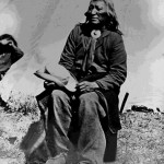 132. Washakie seated outside his tipi hat in hand