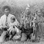 200. Indian men and children one in Anglo dress one in traditional –peyote rattle. Girl in elk tooth dress
