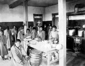 1. Doing chores in kitchen at the Government School - matron standing in the background