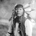 "62. ""Natgoo / Shoshone Chief J.E. Stimson Cheyenne, Wyo Copyright 1900  in eagle feather headdress, kerchief around neck, vest and tied arm bands"