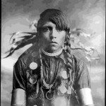 "64. Another Shoshone man in ceremonial headgear with eagle down and moon shell necklace, metal arm bands, 2 strands of beads as a neck choker – ""Moobe"""