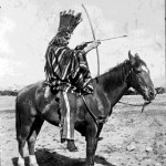 99. Lyman (white man dressed as an Indian on a horse holding bow and arrow – feather headdress)