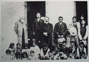 "alt=""agency school--standing from left to right are the Right Reverend John F. Spaulding, Episcopal Bishop of Colorado & Wyoming; teacher Arthur C. Jones, who later became a Laramie banker; the Reverend John Roberts, Episcopal missionary to the reservation; and Sherman Coolidge, an Arapaho who later became an ordained priest. Children are unidentified"""