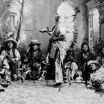 107. Studio shot of Washakie standing with pipe and leaders sitting