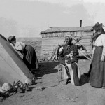 122. Washakie seated outside his cabin with white woman looking into tipi – tipi pegs and rocks showing