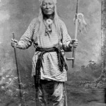 125. Washakie portrait standing studio shot with rifle and pipe