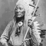 126. Washakie portrait seated with pipe and war bonnet – round scarf tie formal
