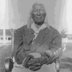 130. Washakie seated in chair outside gov. buildings